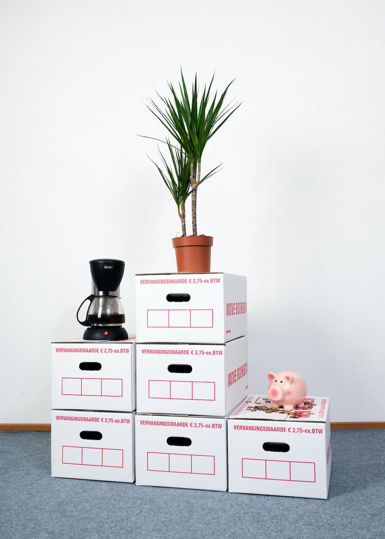 Een podium gemaakt van verhuisdozen hebben op de posities: een plant, koffieapparaat en spaarvarken.