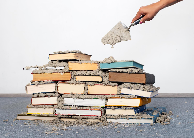 Gemetseld muurtje van boeken. Die de brug tussen brug de schoolbanken en het werkveld symboliseert.